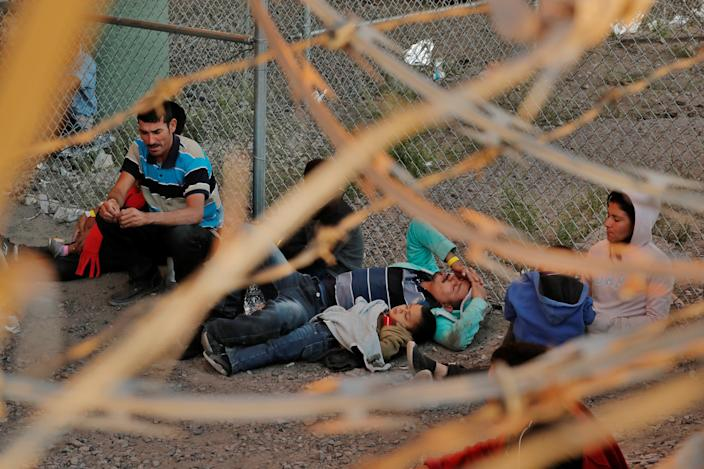 A man and child lie on the ground inside an enclosure, where they are being held by U.S. Customs and Border Protection (CBP), after crossing the border between Mexico and the United States illegally and turning themselves in to request asylum, in El Paso, Texas, U.S., March 29, 2019. (Photo: Lucas Jackson/Reuters)