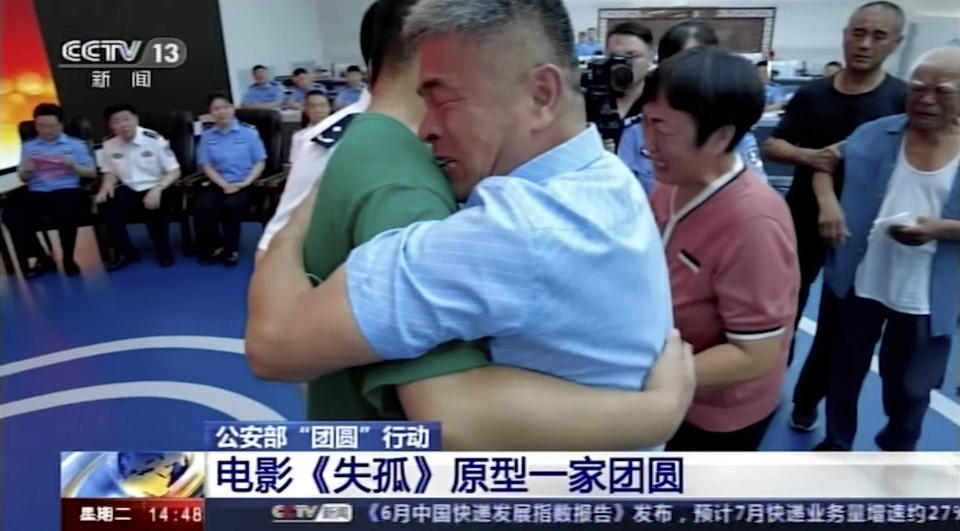 Guo Gangtang at right embraces his long lost son Guo Xinzhen. Source: AP