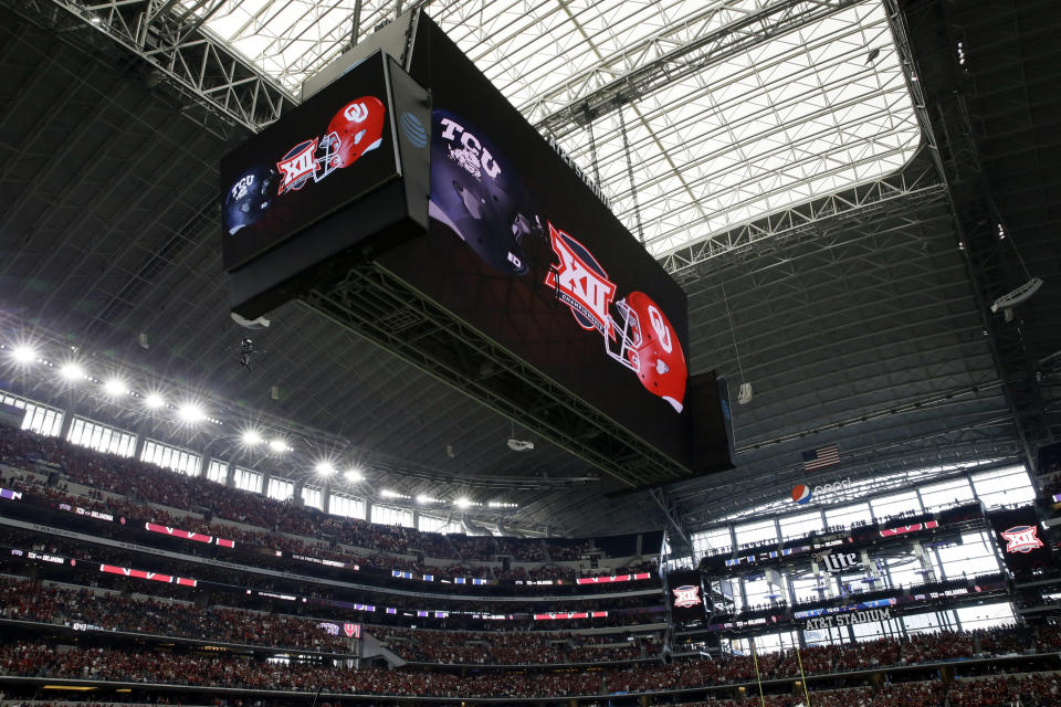 FILE - In this Dec. 2, 2017, file photo, the video screen inside AT&T Stadium displays the TCU and Oklahoma logo's during the first half of the Big 12 Conference championship NCAA college football game in Arlington, Texas. The Big 12 has extended membership invitations to BYU, UCF, Cincinnati and Houston to join the Power Five league. That comes in advance of the league losing Oklahoma and Texas to the Southeastern Conference. (AP Photo/Tony Gutierrez, File)