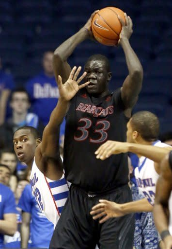 Cincinnati center David Nyarsuk (33) grabs a defensive rebound over DePaul guard Charles McKinney, left, during the first half of an NCAA college basketball game, Tuesday, Jan. 15, 2013, in Rosemont, Ill. (AP Photo/Charles Rex Arbogast)
