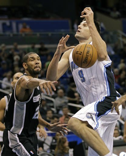 San Antonio Spurs' Tim Duncan, left, knocks the ball from the hands of Orlando Magic's Nikola Vucevic (9), of Montenegro, during the first half of an NBA basketball game, Wednesday, Nov. 28, 2012, in Orlando, Fla. (AP Photo/John Raoux)