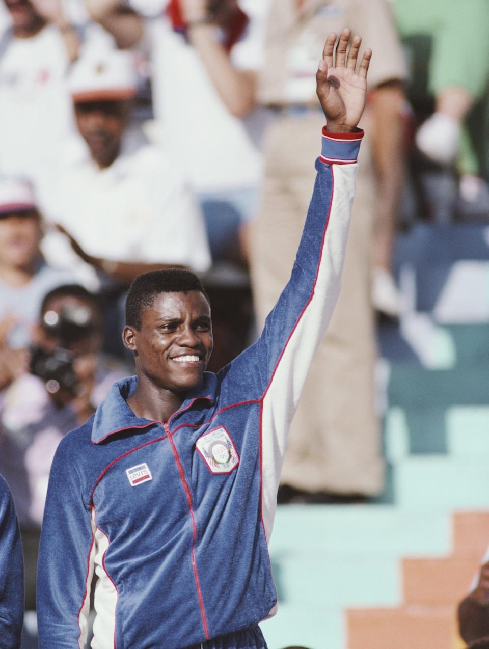 Carl Lewis in tracksuit with arm in the air in 1984.