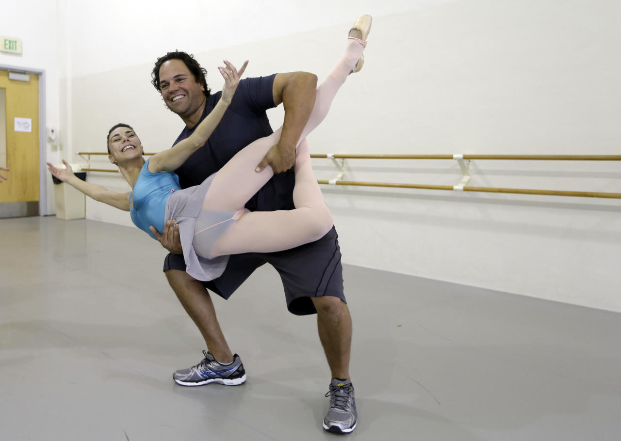 """Former MLB baseball player Mike Piazza poses for a photograph with Miami City ballet principal dancer Patricia Delgado before a rehearsal of """"Slaughter on Tenth Avenue"""" at the Miami City Ballet, Tuesday, April 16, 2013, in Miami Beach, Fla. Piazza will play a gangster in the ballet on May 3. He will say a few lines and then watch the rest of the performance from a seat onstage. Piazza says his turn with the troupe is his gift to his 6-year-old daughter, a student at Miami City Ballet School. (AP Photo/Lynne Sladky)"""