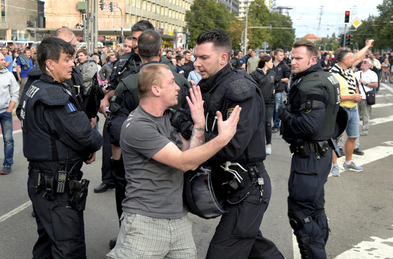 "A police officer pushes a man during a demonstration in Chemnitz, Germany, Monday, Aug. 27, 2018 after a man has died and two others were injured in an altercation between several people of ""various nationalities"" in the eastern German city of Chemnitz on Sunday. Slogan reads 'No Access For Terror'. (AP Photo/Jens Meyer)"