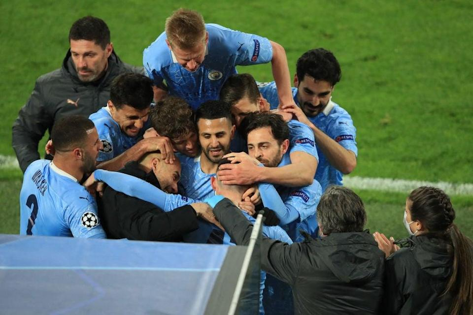 <p>Foden's teammates and manager mob him after City's second goal</p> (AFP via Getty Images)