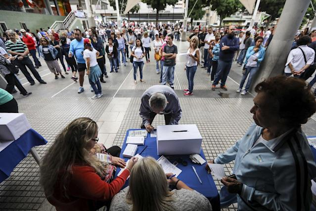 <p>Venezuelan cast their vote during a poll called 'popular consultation' at Colon Square in in Caracas, Venezuela on 16 July 2017. Venezuelans are able to vote organised by the opposition to express their support or rejection to the plan by President Nicolas Maduro to rewrite the constitution through an election of a citizens' body on July 30, 2017. (Miguel Gutierrez/EPA/REX/Shutterstock) </p>