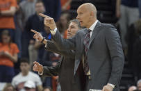 Louisville coach Chris Mack, front, and assistant Dino Gaudio gesture during the second half of the team's NCAA college basketball game against Virginia in Charlottesville, Va., Saturday, March 7, 2020. (AP Photo/Lee Luther Jr.)