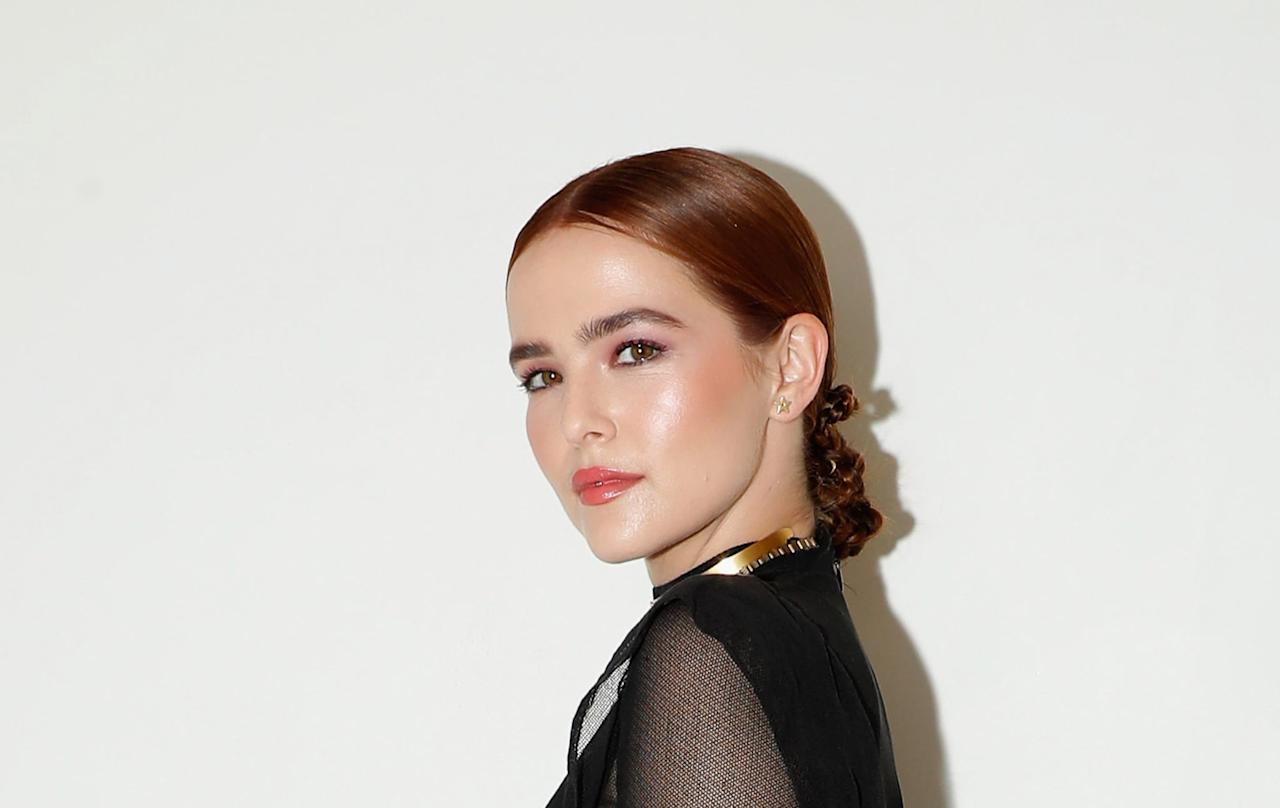 <p>Zoey Deutch twisted, twisted, and twisted some more to get her low knotted ponytail. The hair was likely first parted in the middle and smoothed back into a low ponytail using lots of hairspray. Then the tail was twisted tight until it looped back onto itself to form the knotted pony.</p>