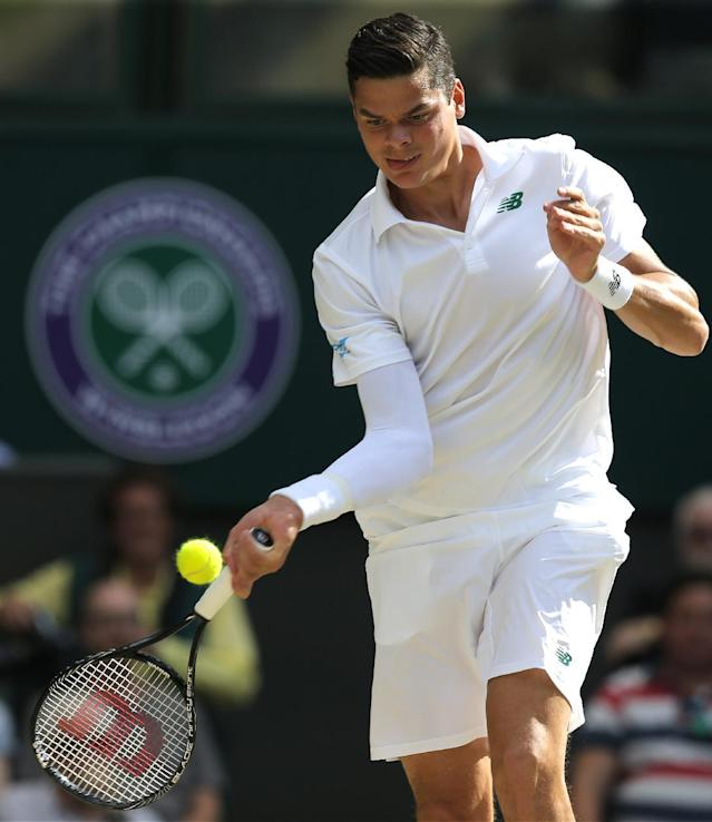 Milos Raonic of Canada plays a return to Roger Federer of Switzerland during their men's singles semifinal match during their match at the All England Lawn Tennis Championships in Wimbledon, London, Friday, July 4, 2014. (AP Photo/Pavel Golovkin)