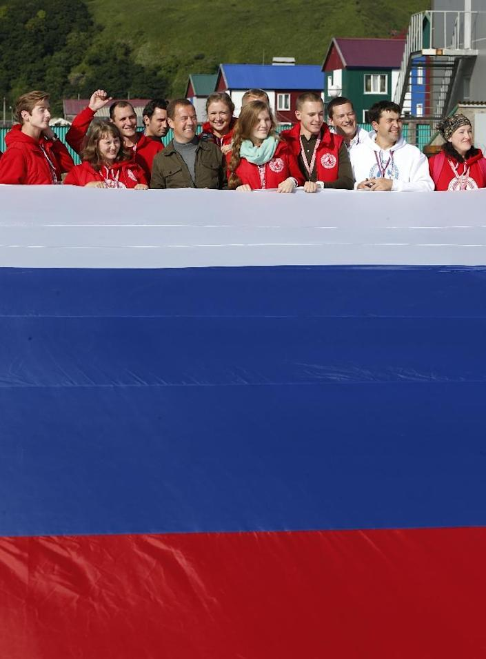 """Russian Prime Minister Dmitry Medvedev (5thL) poses for a picture with participants of the all-Russian youth educational forum """"Iturup"""" in Kurilsk during his visit to Iturup island, on August 22, 2015 (AFP Photo/Dmitry Astakhov)"""