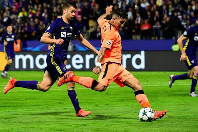 Liverpool's Roberto Firmino (R) runs with the ball past Maribor's Mitja Viler during their UEFA Champions League Group E first leg match, at the Ljudski vrt Stadium in Maribor, Slovenia, on October 17, 2017