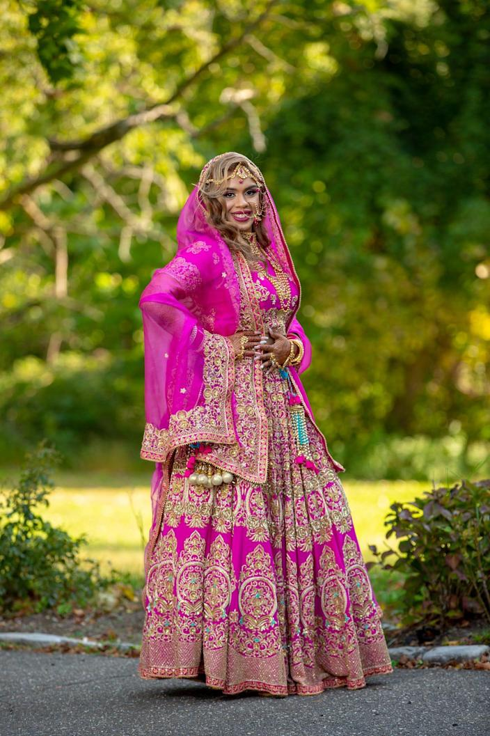 A bride stands in her pink bridal lehenga.
