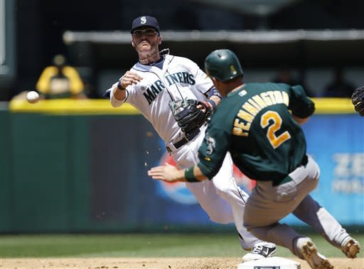 Seattle Mariners shortstop Brendan Ryan, left, throws to first after forcing out Oakland Athletics' Cliff Pennington at second base in the fourth inning of a baseball game, Wednesday, June 27, 2012, in Seattle. Josh Reddick was out at first on the double play. (AP Photo/Elaine Thompson)