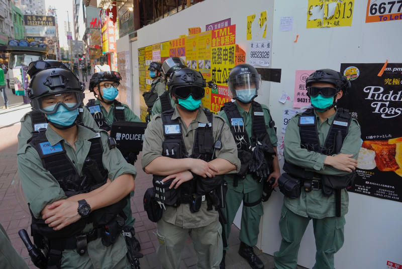 Police officers stand guard as people gather during a pro-democracy rally supporting human rights and to protest against Beijing's national security law in Hong Kong, Sunday, June 28, 2020. (AP Photo/Vincent Yu)