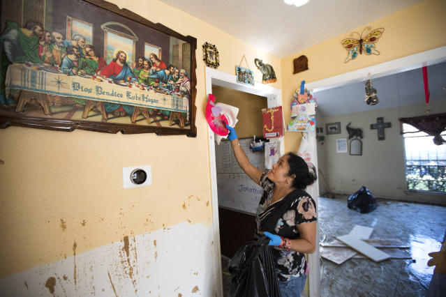 <p>Alma Castenda pulls her children's artwork off the walls as she cleans up her flood-damaged home in the Verde Forest subdivision of Houston in the aftermath of Tropical Storm Harvey on Thursday, Aug. 31, 2017. (Photo: Brett Coomer/Houston Chronicle via AP) </p>