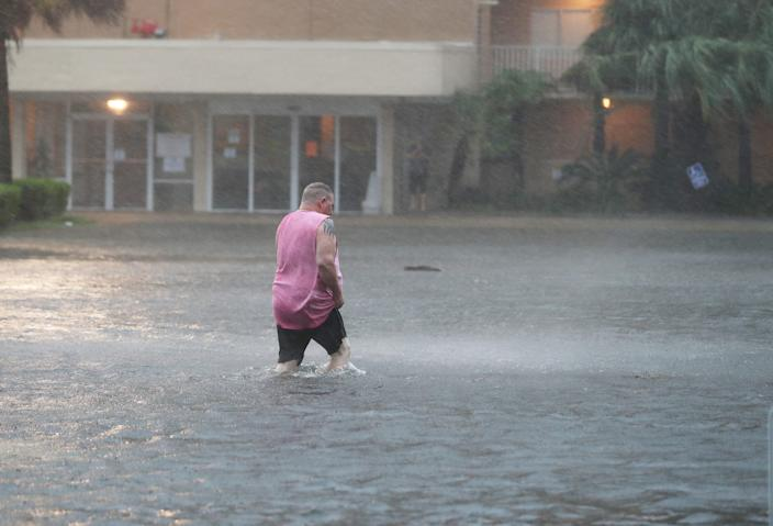 """A man walks through a flooded parking lot in Gulf Shores, Alabama as the outer bands of Hurricane Sally come ashore on September 15, 2020. <p class=""""copyright"""">Joe Raedle/Getty Images)</p>"""