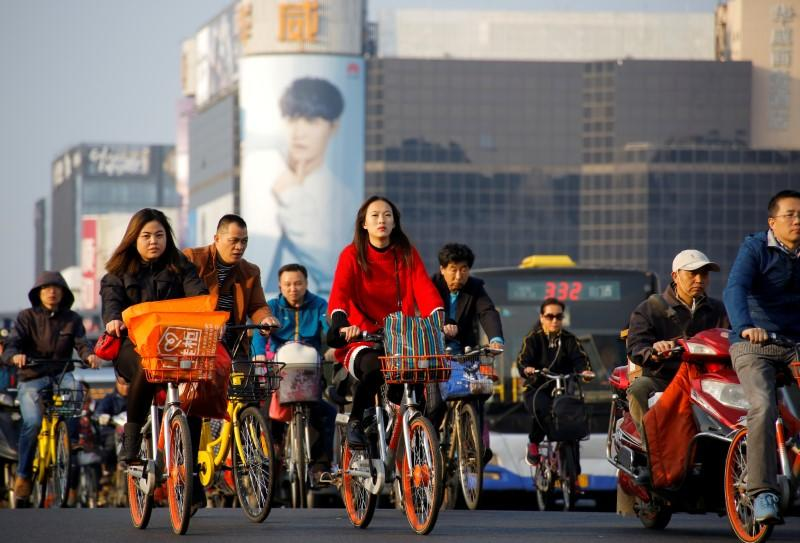 FILE PHOTO: People cross a busy street on bicycles and electric scooters in central Beijing