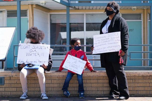 PHOTO: Kizzy Jones, a co-founder of Memphis Community Against the Pipeline, holds signs outside the National Civil Rights Museum with her family during a rally against the construction of the Byhalia Connection Pipeline, Feb. 23, 2021, in Memphis, Tenn. (Commercial Appeal via USA Today Network, FILE)