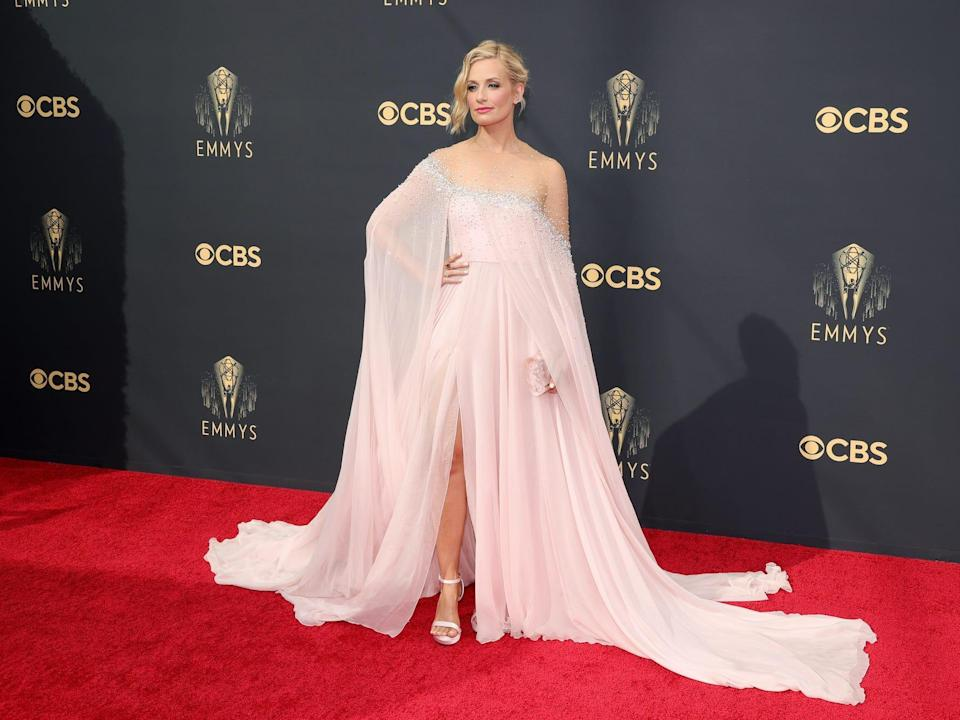 Beth Behrs wears a pink dress on the Emmys red carpet.
