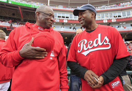 Cincinnati Reds manager Dusty Baker, left, talks with former NFL football player Cris Carter prior to a baseball game against the Atlanta Braves, Monday, May 6, 2013, in Cincinnati. Carter attended to throw out a ceremonial first pitch. (AP Photo/Al Behrman)