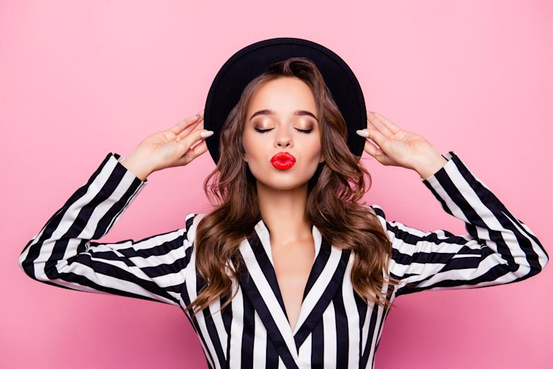 Nice, rich, independent, confident, successful, luxury, sexy girl holding hat on her head with hands, having closed eyes, blowing kiss to the camera, isolated on pink background