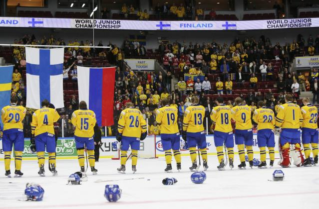 Sweden's team watch the flag of Finland being raised for the after losing in overtime of their IIHF World Junior Championship gold medal ice hockey game in Malmo, Sweden, January 5, 2014. REUTERS/Alexander Demianchuk (SWEDEN - Tags: SPORT ICE HOCKEY)