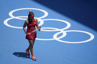 FILE - In this July 25, 2021 file photo Naomi Osaka, of Japan, inspects her racket during a tennis match against China's Zheng Saisai at the 2020 Summer Olympics, in Tokyo, Japan. Osaka and Simone Biles are prominent young Black women under the pressure of a global Olympic spotlight that few human beings ever face. But being a young Black woman -- which, in American life, comes with its own built-in pressure to perform -- entails much more than meets the eye. (AP Photo/Patrick Semansky, File)