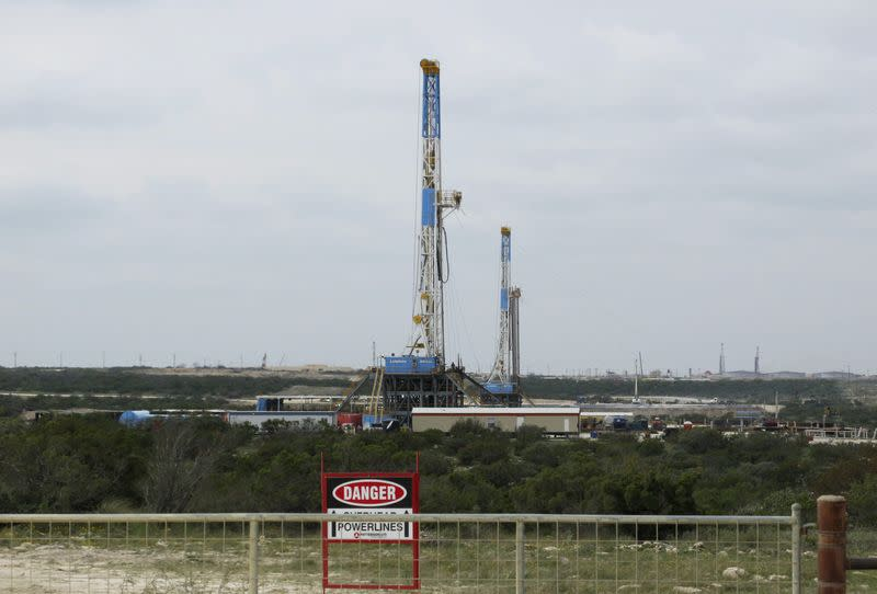 File photo of rigs contracted by Apache Corp drill for crude oil locked tight in shale in west Texas' Permian Basin near the town of Mertzon