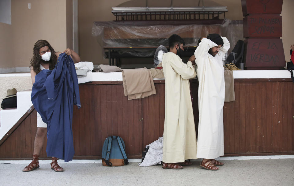 Actors put on their costumes prior a Palm Sunday passion play amid the coronavirus pandemic, outside Iztapalapa Cathedral, in Iztapalapa, a borough of Mexico City, Sunday, March 28, 2021. (AP Photo/Marco Ugarte)