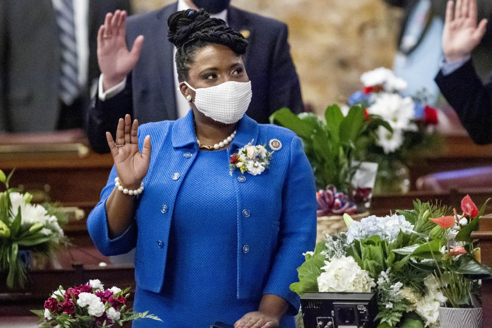 FILE - In this Jan. 5, 2021 file photo, incoming House Minority Leader Joanna McClinton, D-Philadelphia, raises her hand as the Pennsylvania House of Representatives is sworn-in at the state Capitol in Harrisburg, Pa. After only their first few weeks of work, tensions already are high among lawmakers meeting in-person at some state capitols — not because of testy debates over taxes, guns or abortion, but because of a disregard for coronavirus precautions. (AP Photo/Laurence Kesterson, File)