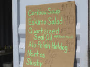 This July 4, 2014, photo provided by Val Kreil shows a restaurant menu of food for sale, including Caribou soup, Eskimo Salad and Seal Oil at the community fairgrounds in Kotzebue, Alaska. The Maniilaq Health Association in the Chukchi Sea community of Kotzebue has received state approval to process and serve seal oil at its elder care facility in Kotzebue, believed to be a first for seal oil in the U.S. (Val Kreil via AP)