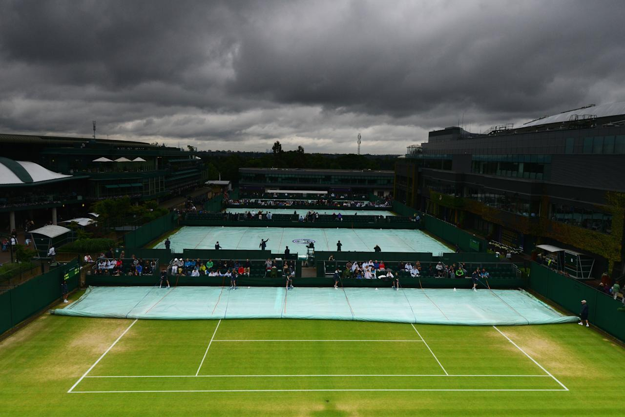 LONDON, ENGLAND - JUNE 28: (EDITORS NOTE: A neutral density camera filter was used for this image.) Groundstaff remove the covers from court fourteen on day five of the Wimbledon Lawn Tennis Championships at the All England Lawn Tennis and Croquet Club on June 28, 2013 in London, England. (Photo by Mike Hewitt/Getty Images)
