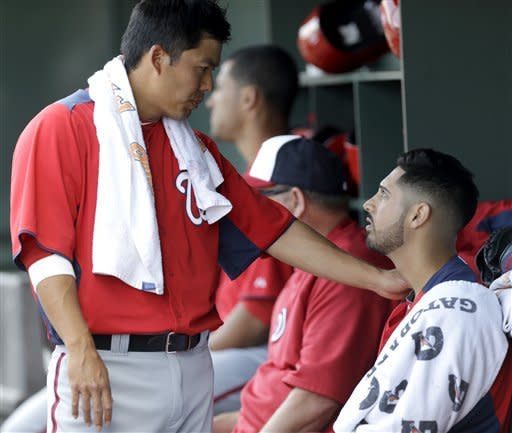 Washington Nationals' Kurt Suzuki, left, talks to pitcher Gio Gonzalez in the dugout during the second inning of an exhibition spring training baseball game against the St. Louis Cardinals, Saturday, March 2, 2013, in Jupiter, Fla. (AP Photo/Julio Cortez)