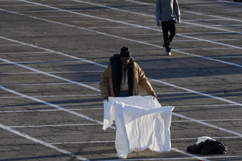 People prepare places to sleep in areas marked by painted boxes on the ground of a parking lot at a makeshift camp for the homeless Monday, March 30, 2020, in Las Vegas. Officials opened part of the lot as a makeshift homeless shelter after a local shelter closed when a man staying there tested positive for the coronavirus. (AP Photo/John Locher)