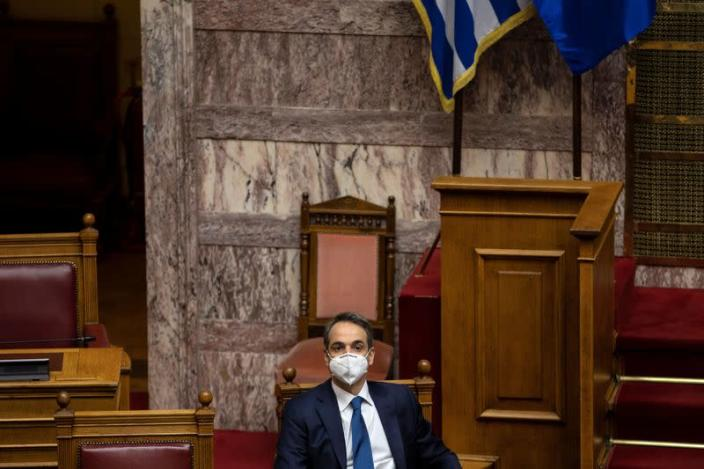 Greek PM Mitsotakis wears a protective face mask during a parliamentary session on revelations of abuse in arts and sports, in Athens