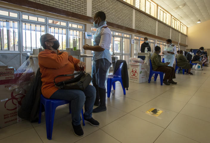 Thoko Hlongwane, waits to be vaccinated as a nurse prepares a dose of the Pfizer COVID-19 vaccine at Chris Hani Baragwanath Academic Hospital in Soweto, South Africa, Monday, May 17, 2021. South Africa has started its mass vaccination drive with the goal of inoculating nearly 5 million citizens aged 60 and above by the end of June. (AP Photo/Themba Hadebe)