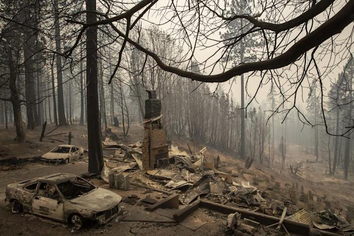 """The ruins of a home in Brush Creek in Butte County smolder Thursday. <span class=""""copyright"""">(Brian van der Brug / Los Angeles Times)</span>"""