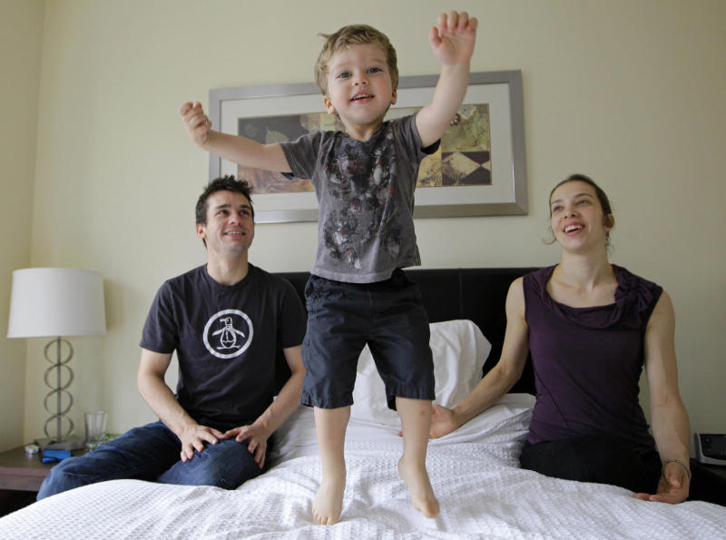 "This June 14, 2012 photo shows Cirque du Soleil ""Zarkana"" performers Jeremie Robert, left, and Julie Dionne play with their two-and-a-half year-old son Émile in their temporary apartment in New York. The couple, who are performing in New York City through September, met and fell in love while doing another Cirque du Soleil show. (AP Photo/Kathy Willens)"