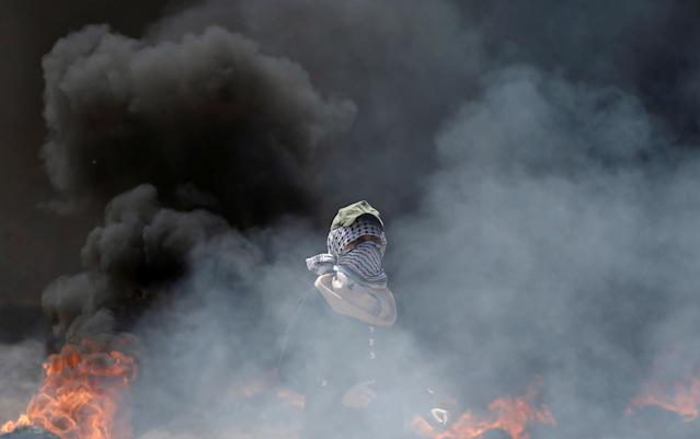 <p>A female Palestinian demonstrator stands amid smoke during a protest against the U.S. Embassy's move to Jerusalem and ahead of the 70th anniversary of Nakba, at the Israel-Gaza border east of Gaza City on May 14, 2018. (Photo: Mohammed Salem/Reuters) </p>