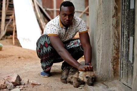 Abbas Yusuf, 23, known as Hyena Man, plays with a hyena cub near his house within the walled city of Harar, Ethiopia, February 25, 2017. REUTERS/Tiksa Negeri
