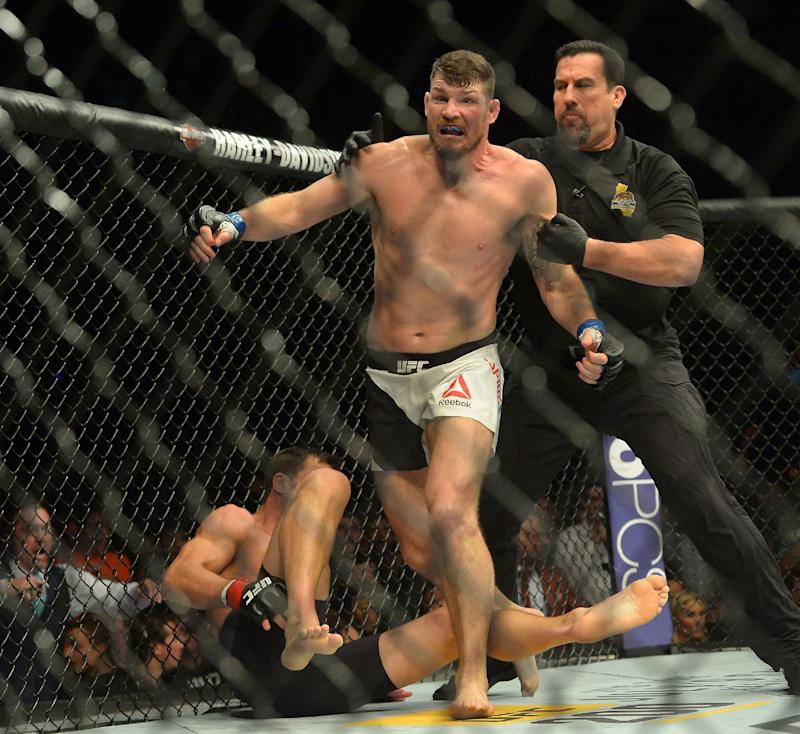 Michael Bisping is pulled off Luke Rockhold after knocking him out to win the UFC middleweight title at UFC 199.