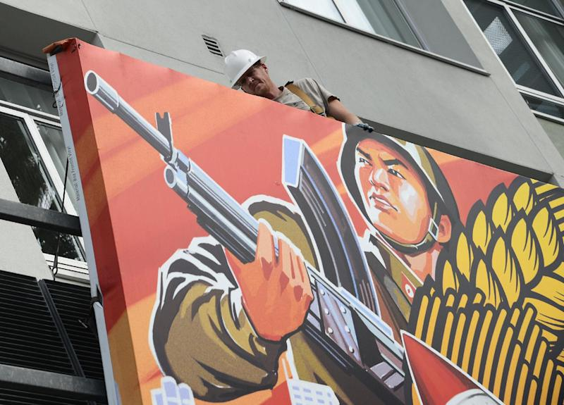 "Workers remove a poster for ""The Interview"" from a billboard in Hollywood, California, December 18, 2014 (AFP Photo/Robyn Beck)"