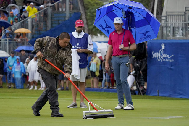 A course worker clears standing water off the 18th green before Bo Hoag putts during the final round of the Sony Open PGA Tour golf event, Sunday, Jan. 12, 2020, at Waialae Country Club in Honolulu. (AP Photo/Matt York)