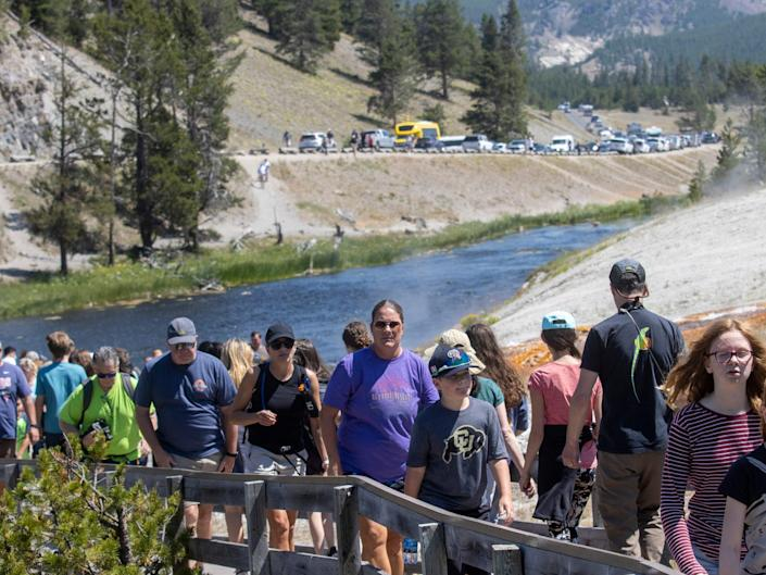 A long line of people on a trail at Yellowstone, with a river in the background and a road full of cars.
