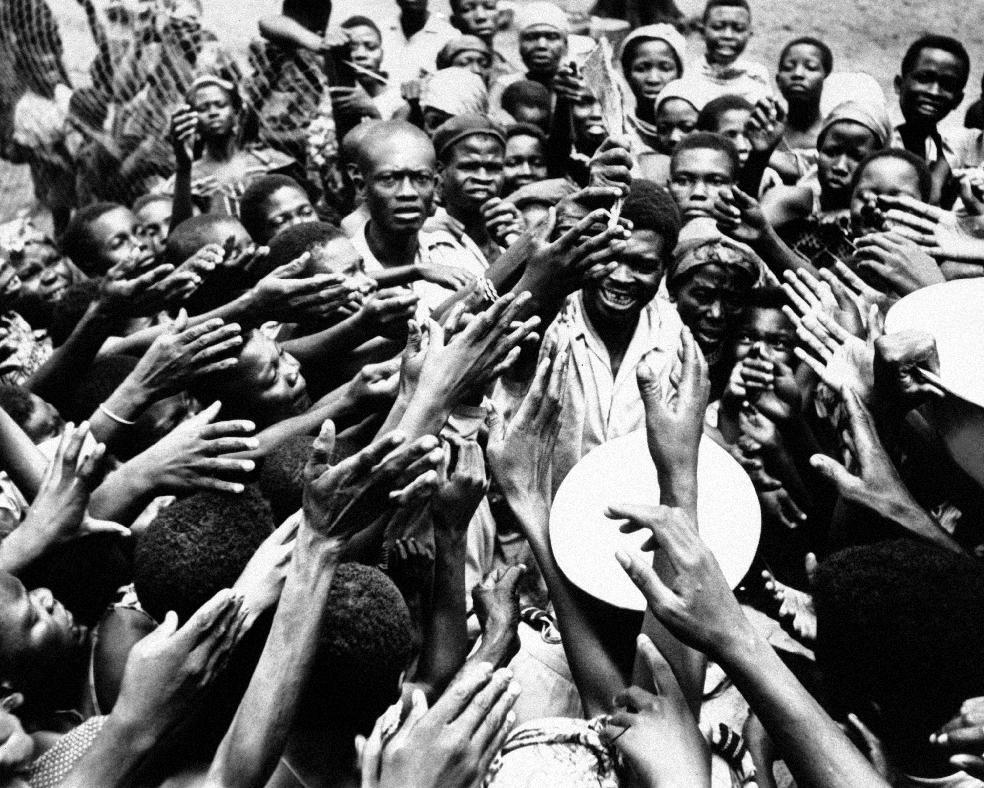 FILE - In this Jan. 26, 1961 file photo, scores of eager hands reach towards the Congolese official who distributes small rations of dried fish and palm oil to people at the hospital in Miabi, South Kasai, Congo. Faas, a prize-winning combat photographer who carved out new standards for covering war with a camera and became one of the world's legendary photojournalists in nearly half a century with The Associated Press, died Thursday May 10, 2012. He was 79. (AP Photo/Horst Faas, File)