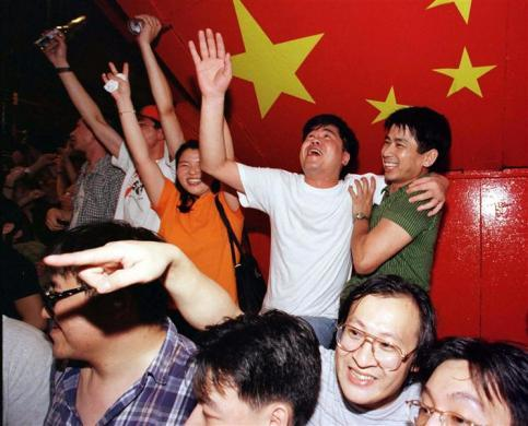 Revelers in Lan Kwai Fong in central Hong Kong celebrate in the streets the handover of sovereignty to China at the stroke of midnight July 1, Bobby Yip. The handover of Hong Kong ends 156 years of British colonial rule.