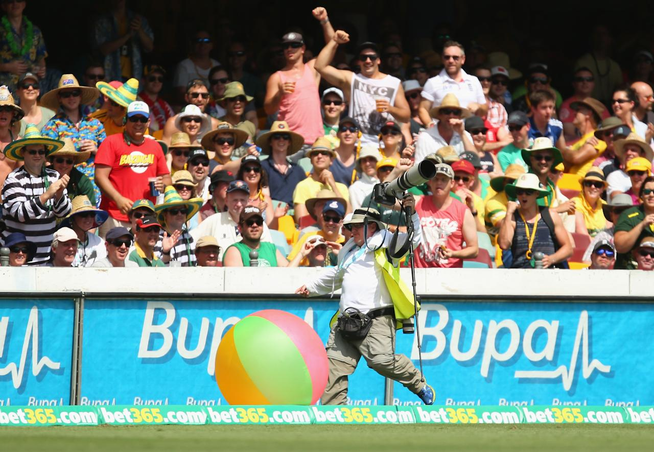 BRISBANE, AUSTRALIA - NOVEMBER 23:  A photographer kicks a beachball back into the crowd during day three of the First Ashes Test match between Australia and England at The Gabba on November 23, 2013 in Brisbane, Australia.  (Photo by Scott Barbour/Getty Images)