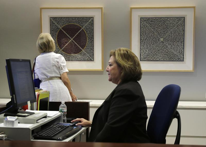 Two prints from Sharon Sutton's Space Time series hang in the office of the CEO of Johnson & Johnson in New Brunswick, N.J. on Tuesday, July 30, 2013. The prints are part of the art collection displayed throughout the world headquarters. Corporation art collecting has a long history that can be traced to the 1400s when European banks commissioned artists to create murals. But using art as part of a company's business plan is a modern concept in North America that emerged at the turn of the 20th century. (AP Photo/Mel Evans)