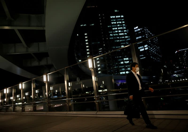 FILE PHOTO: A worker wearing a protective face mask walks past office buildings in the background, during the global outbreak of the coronavirus disease (COVID-19), in Tokyo