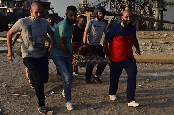 People carry a wounded man after a fire at a warehouse with explosives at the Port of Beirut led to massive blasts in Beirut
